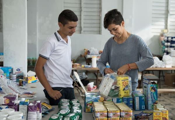 Natalie Maldonado (dcha.) y su hermano Danni de la Parroquia San Miguel Arcángel, en Utuado, empacan alimentos para luego repartirlos a los damnificados del huracán María. (Octavio Durán OFM/Puerto Rico)