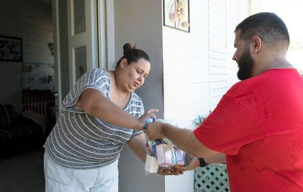 Un voluntario de la parroquia San Miguel Arcángel en Utuado, entrega lleva ayuda al hogar de una familia afectada por el Huracán Maria. (Octavio Durán OFM/Puerto Rico)