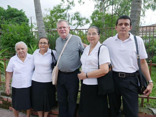 Miembros del ministerio para los enfermos de la parroquia Cristo Salvador y el padre Northrop brindan consuelo espiritual a enfermos en El Salvador.