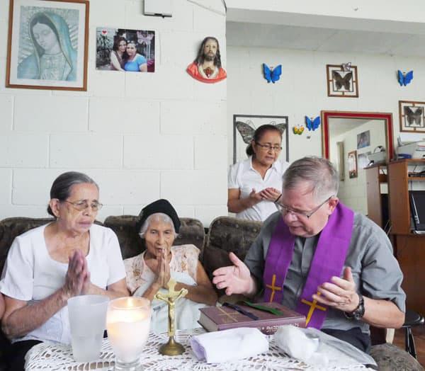 El sacerdote y agentes pastorales visitan a María Alicia Guzmán, 92, para rezar juntos, como parte de su ministerio de visita a los enfermos