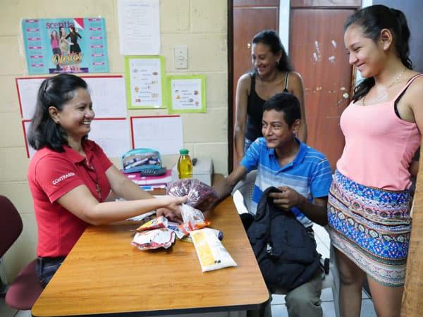 Hermana Maryknoll Gloria Agnes Ardenio (izq.) distribuye comida a una familia en la clínica ContraSida, la cual atiende a pacientes con VIH/ SIDA.