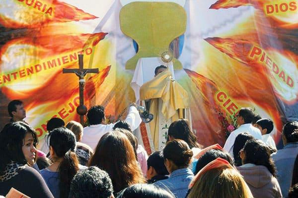 El Padre Enrique Bustamante alza al Santísimo durante la celebración de Corpus Christi en la parroquia San Pío X en Cochabamba, Bolivia
