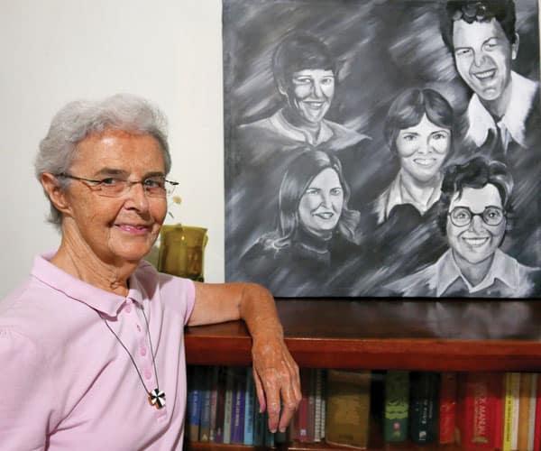 Hermana Brennan posa al lado de una pintura de misioneras que murieron el El Salvador. Ella ofrece un ministerio en las prisiones