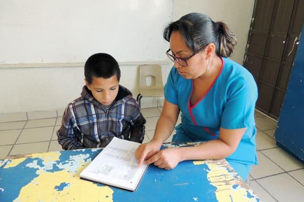 Julia Gutiérrez, tutora del centro y una de las mujeres de Ciudad Juarez, ayuda a un niño a hacer sus tareas