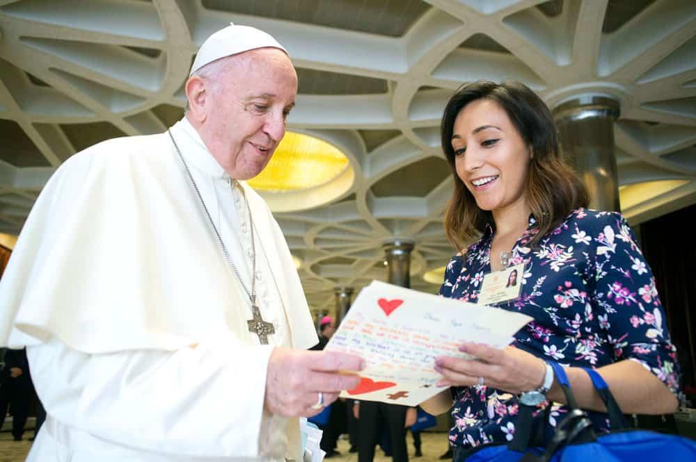 Yadira Vieyra, una de las 34 auditores jóvenes durante el sínodo, le entrega al Papa Francisco una carta escrita por niños. (CNS/Ciudad del Vaticano)