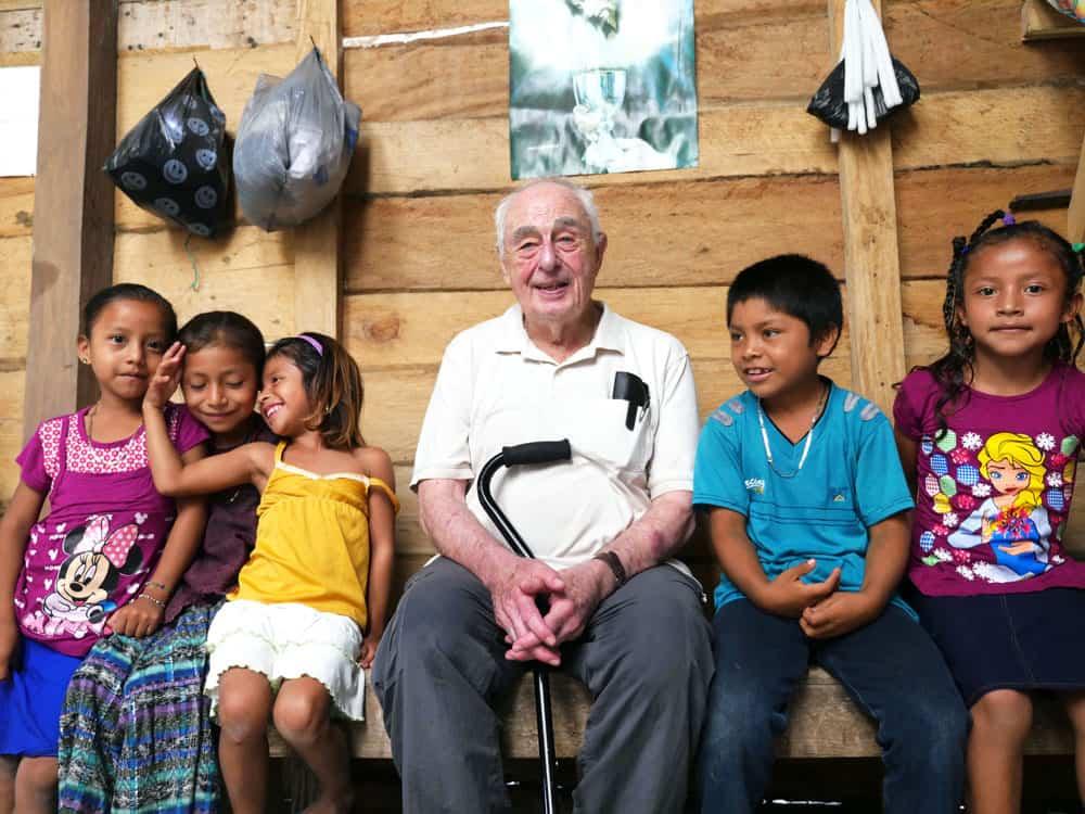 Sacerdote de los Maya El padre Mullan conversa con niños q'eqchi' después de la Misa dominical en la aldea el Limón. (Sean Sprague/Guatemala)