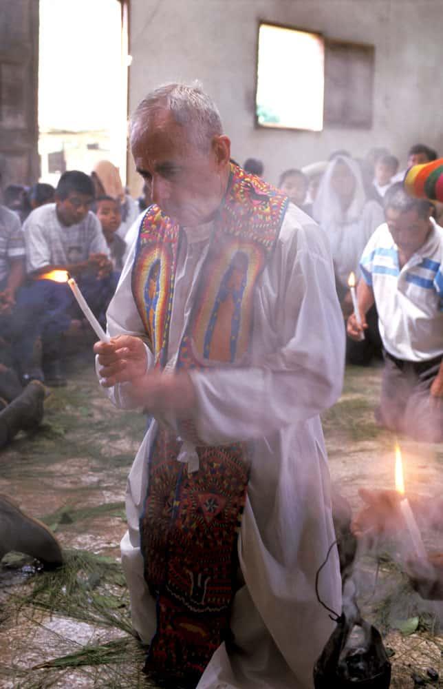 Sacerdote de los Maya En esta foto del 2001, el padre Mullan y la comunidad maya se arrodilla durante la Misa. (Sean Sprague/Guatemala)