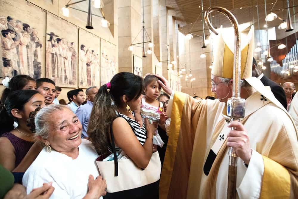ex inmigrante indocumentado-El arzobispo Gómez bendice a una niña en una Misa de reconocimiento a los inmigrantes en la Catedral de Nuestra Señora de Los Ángeles. (CNS/Los Ángeles)