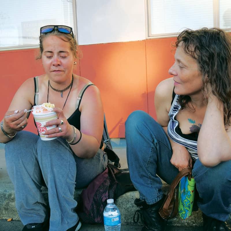 Dos mujeres sin hogar en Everett . reciben alimentos y servicios ofrecidos por voluntarios de MercyWatch.