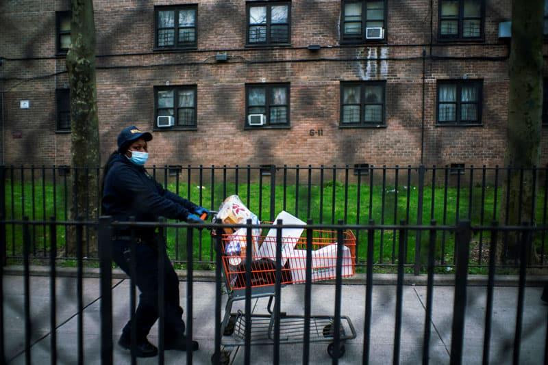 """Pandemia acentúa disparidades a lo largo de líneas raciales, étnicas: Una mujer en la ciudad de Nueva York empuja su carrito de comida donada el 15 de abril de 2020, durante la pandemia de coronavirus. Los Centros para el Control y la Prevención de Enfermedades dijeron en una declaración reciente que """"los datos actuales sugieren una carga desproporcionada de enfermedad y muerte entre los grupos minoritarios raciales y étnicos"""", particularmente los latinos y los afroamericanos. (Foto del CNS / Eduardo Muñoz, Reuters)"""