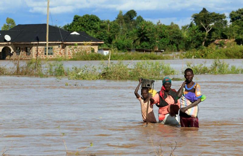 Residentes caminan a través de las inundaciones en Budalangi, Kenya, el 3 de mayo de 2020. Al menos 100 están muertos y miles de personas sin hogar después de fuertes lluvias y tormentas eléctricas que provocaron graves inundaciones y deslizamientos de tierra en Kenya. (CNS, Thomas Mukoya, Reuters/Kenya)