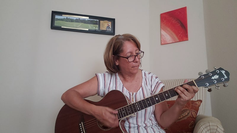 Después de asistir al webinar de Maryknoll y reflexionar sobre un pasaje de la biblia, Iris Lai-Zayas se inspiró para componer y grabar una canción. Ella está tocando la guitarra y cantando en casa durante este tiempo de coronavirus. (Iris Lai-Zayas/Texas)