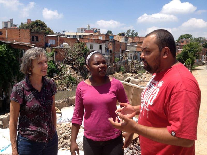 Desastres ambientales: Joanne Blaney (izq.), con la hermana Maryknoll Armeline Sidoine y José Silva, un educador y líder comunitario, en la favela de Capão Redondo, que sufre sequías e inundaciones y tiene altos niveles de violencia urbana y degradación ambiental. (Foto cortesía de Misioneros Laicos Maryknoll/Brasil)