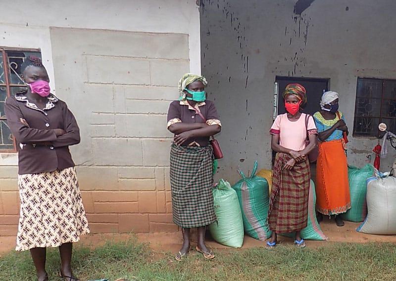 hambre y hambruna: En una estación parroquial en Kenya, mujeres con máscaras protectoras esperan la distribución de alimentos, realizada con el apoyo de los Padres y Hermanos Maryknoll. Muchas personas en Kenya enfrentan escasez de alimentos y posible hambruna a medida que el país cerró en respuesta a la pandemia de COVID-19. (Foto cortesía de Lance Nadeau / Kenya)