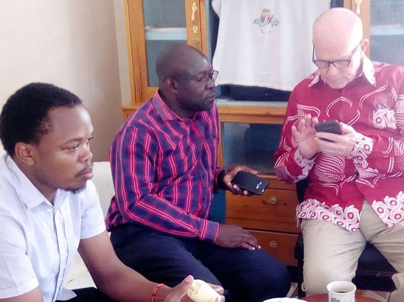 El Padre Maryknoll Joseph Healey explica cómo votar en el sitio web de PCC a dos miembros del Equipo de capacitación de pequeñas comunidades cristianas de AMECEA en Nairobi, Kenya. (Cortesía de Joseph Healey/Kenya)