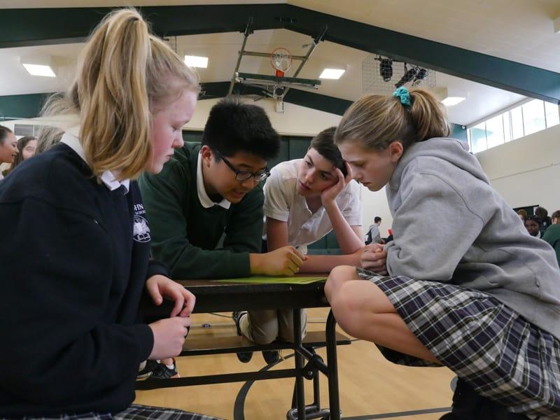MDI: Los estudiantes de séptimo grado trabajan juntos para aprender sobre las situaciones de vida de niños en todo el mundo a través de un juego interactivo en el Día Capstone. (Sean Sprague/Washington)