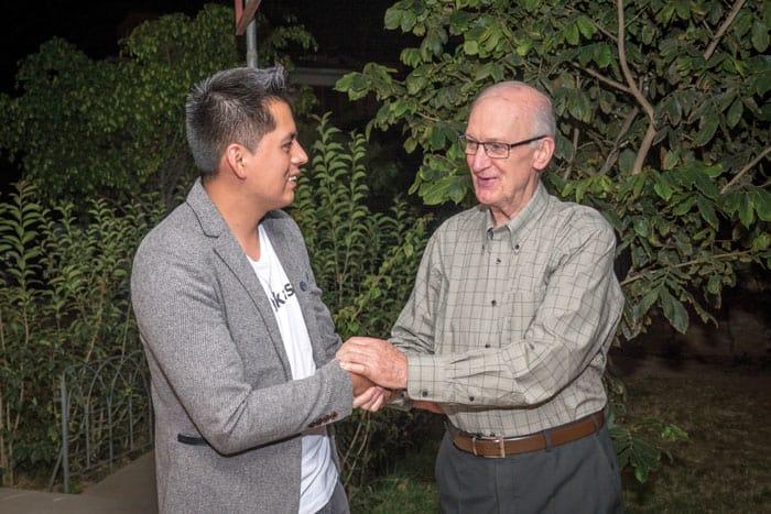 El padre Chapin le da la mano a Ronald Albarez, un joven feligrés y psicólogo, que está apoyando a feligreses de su parroquia a adaptarse a la pandemia de COVID-19, que afecta al mundo. ( Nile Sprague/Bolivia)