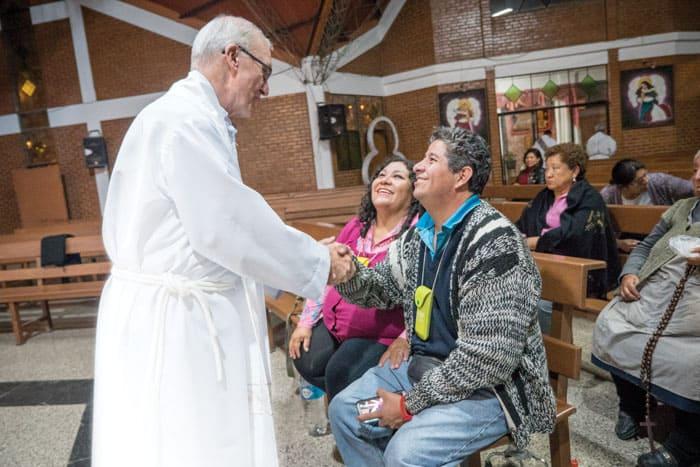 El padre Chapin saluda a feligreses en Bolivia en una forto antes de la pandemia de COVID-19.