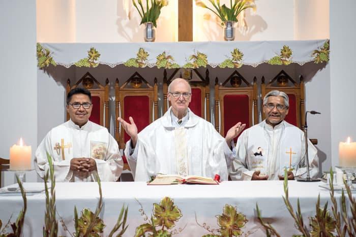 De izq. a dcha.: el Padre David Cardozo, párroco de Nuestra Señora de la Salette, el padre Daniel Chapin y el padre Cruz saludan a los feligreses y están listos para celebrar la misa. (Nile Sprague/Bolivia)