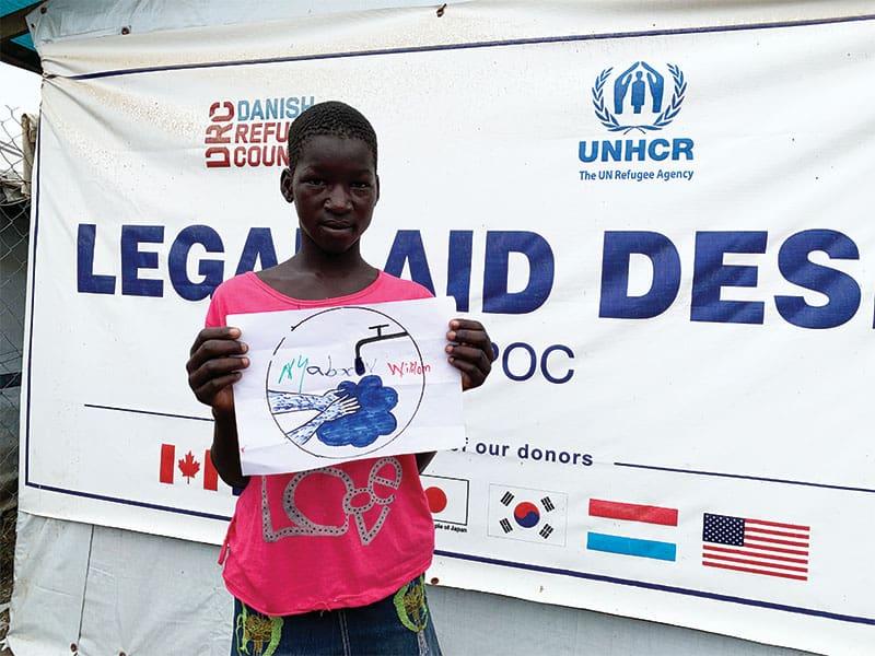 Durante un programa de la ONU sobre concientización ante el COVID-19, una joven muestra su dibujo sobre cómo prevenir la expansión del virus, lavándose las manos con frecuencia.