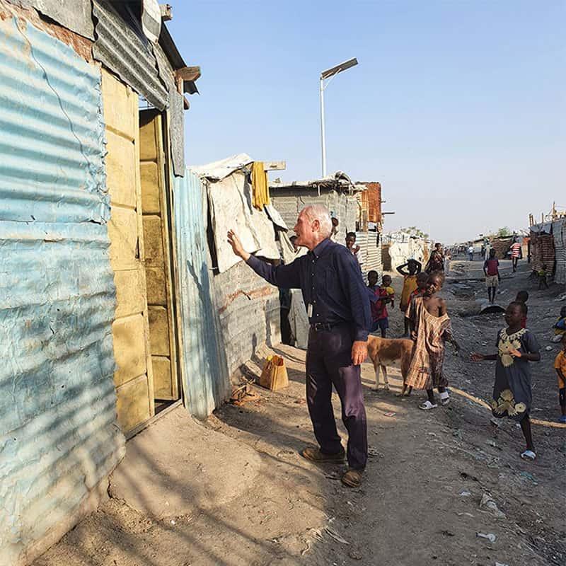 El Padre Maryknoll Michael Bassano saluda a refugiados en un campamento de la ONU en Sudán del Sur.