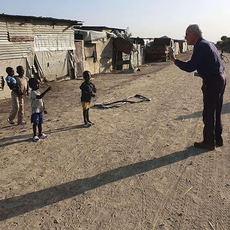 El Padre Maryknoll Michael Bassano saluda a niños en un campamento de la ONU para refugiados en Sudán del Sur.