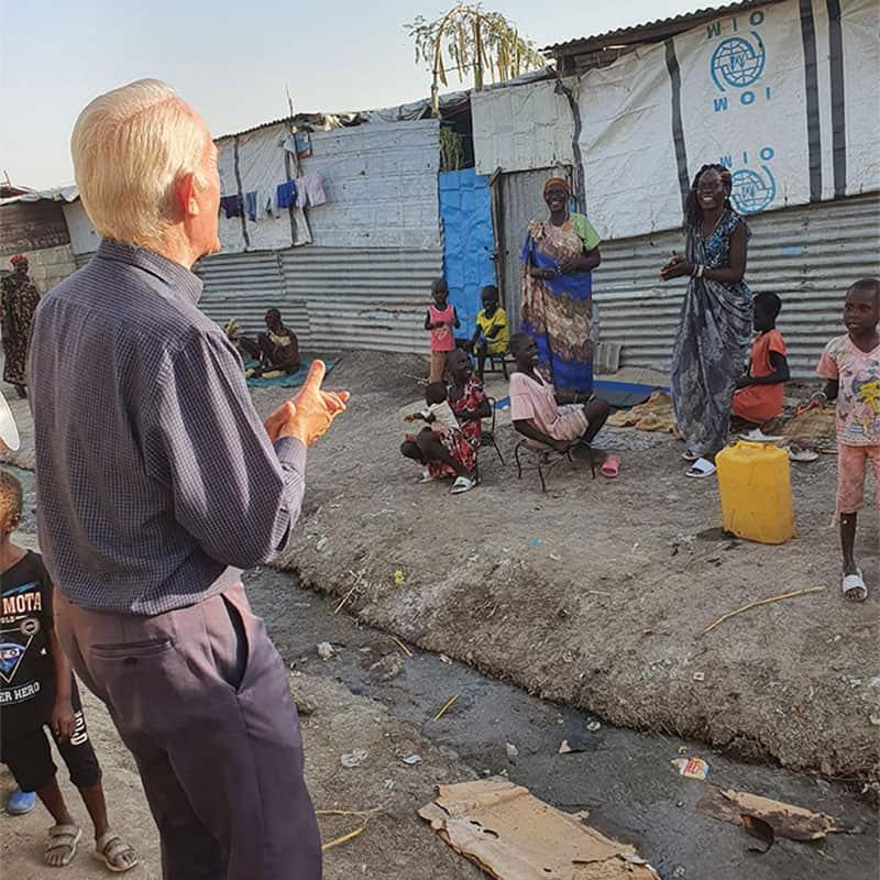 El Padre Maryknoll Michael Bassano mantiene distancia social mientras visita un campamento de la ONU para refugiados en Sudán del Sur.