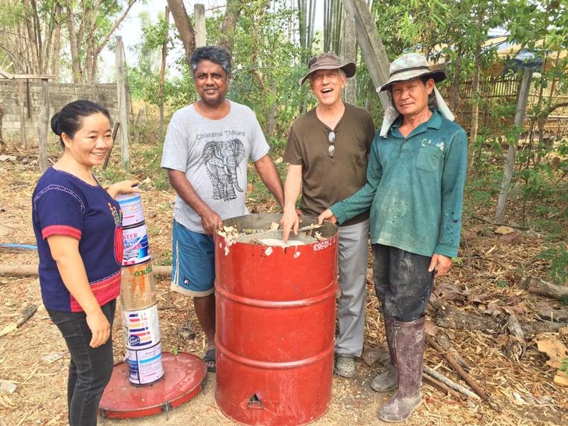 Los miembros del personal de RTRC (de izquierda a derecha) Sra. Phut, Sr. Sornchai, padre Radice y Sr. Manut producen biocarbón quemando material de desecho orgánico. (Cortesía de Lawrence Radice/Tailandia)