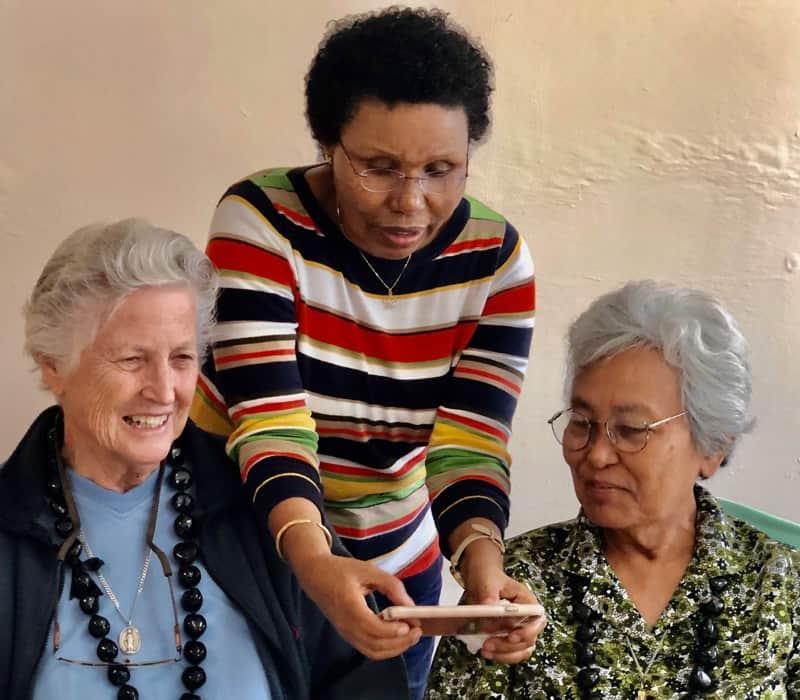 La misionera Bitrina Kirway demuestra las maravillas del iPhone a sus compañeras hermanas Maryknoll Ardis Kremer (izquierda) y Rosalinda Barrozo. (Cortesía de las Hermanas Maryknoll)