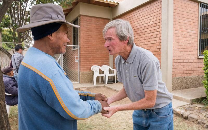 Misionero O'Donoghue saluda a Andrés, un paciente con problemas mentales en el jardín del hogar de las Hermanas de la Caridad en la ciudad de Cochabamba, Bolivia. (NIle Sprague/Bolivia)