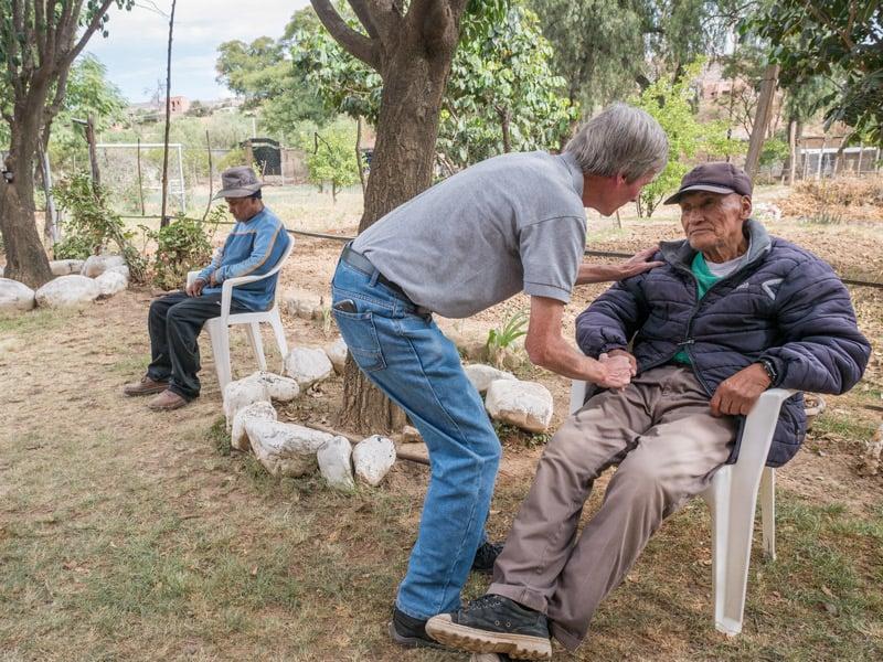 Dcha.: O'Donoghue consuela a Calixto Cejo, un anciano con problemas de audición y ciego de un ojo, en el centro de Cochabamba, Bolivia. Izq.: Andrés, un paciente descansa en el jardín. (NIle Sprague/Bolivia)