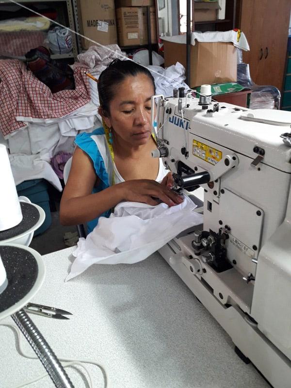 Esmeralda cose botones en camisas de uniformes escolares en la cooperativa ACOMUJERZA, donde ha trabajado durante 15 años y ahora es una de las jefas de costura. (Ana Morales/El Salvador )