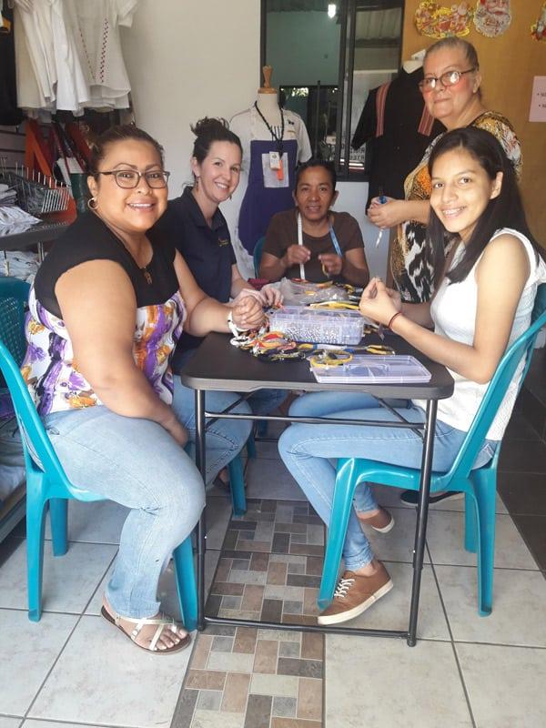 Jóvenes se unen a miembros de la cooperativa ACOMUJERZA para participar en un taller de fabricación de brazaletes. (Rafael Borja/El Salvador)