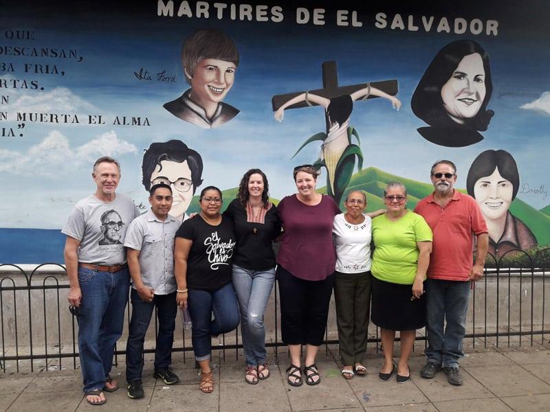 La misionera laica Maryknoll Melissa Altman (cuarta desde la izquierda), miembros de la cooperativa ACOMUJERZA y amigos se paran frente a un mural de cuatro religiosas asesinadas en El Salvador. (Peter Altman/El Salvador)