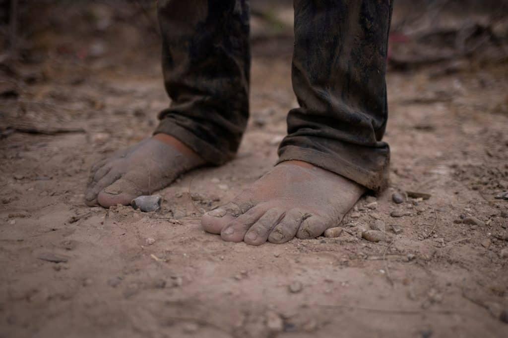 Los pies descalzos de un migrante se ven en La Joya, Texas, el 14 de marzo de 2021, luego de que el migrante cruzara el Río Grande. (Foto del CNS / Adrees Latif, Reuters)