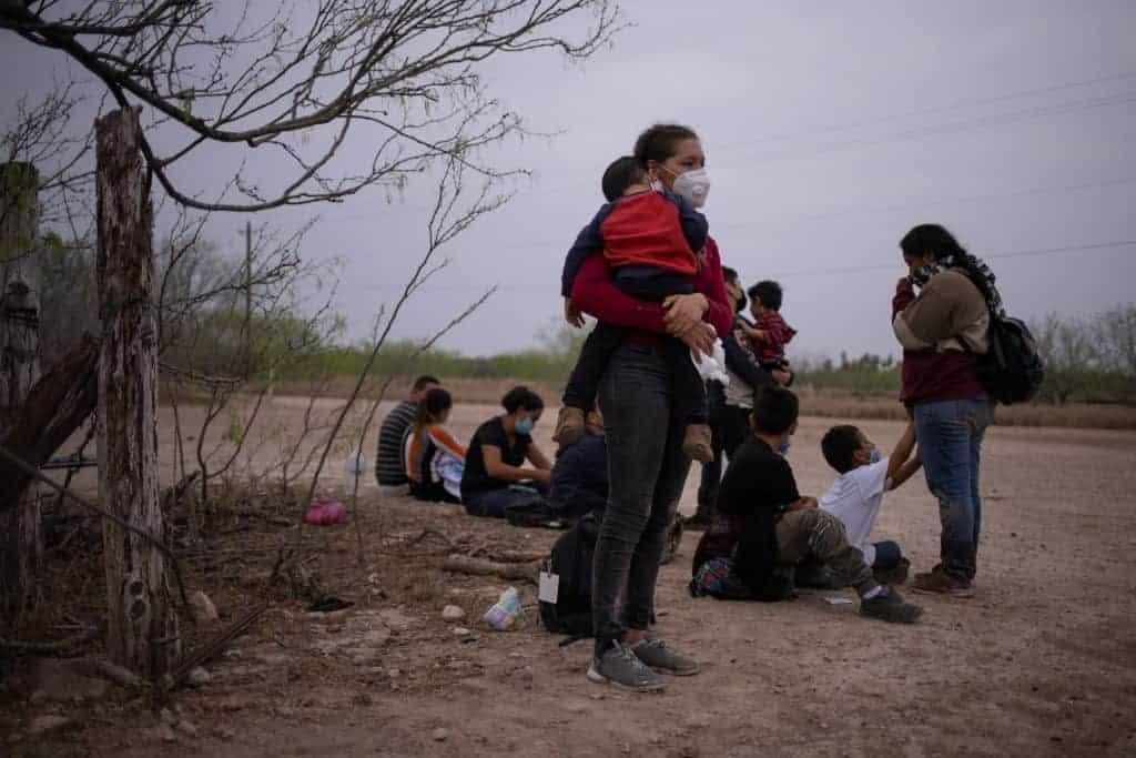 Una madre hondureña de 18 años sostiene a su hijo después de cruzar el río Grande hacia La Joya, Texas, el 14 de marzo de 2021 (foto del CNS / Adrees Latif, Reuters).