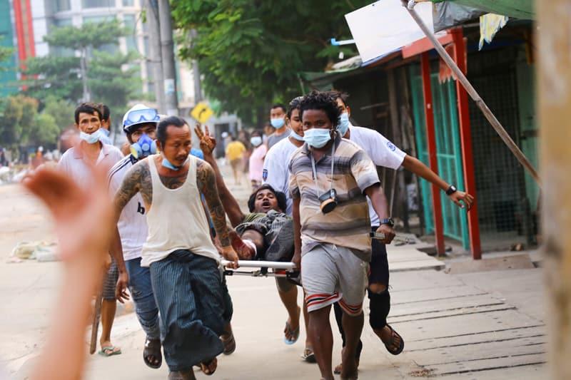 Un hombre que recibió un disparo durante una ofensiva contra manifestantes antigolpistas muestra un saludo de tres dedos mientras lo ayudan en Thingangyun, Yangon, Myanmar, el 14 de marzo de 2021. El 17 de marzo, el Papa Francisco hizo un llamamiento para el fin de la violencia y el inicio de diálogo en Myanmar, donde las fuerzas de seguridad han matado al menos a 138 personas. (Foto del CNS / Reuters)