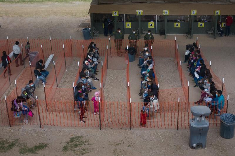 Las familias migrantes de América Central que buscan asilo en los EE. UU. Hacen fila para ser transportadas desde un centro de procesamiento de Aduanas y Protección Fronteriza improvisado debajo del Puente Internacional de Anzalduas después de cruzar el Río Bravo hacia Granjeno, Texas, el 24 de marzo de 2021 (Foto del CNS / Adrees Latif , Reuters)