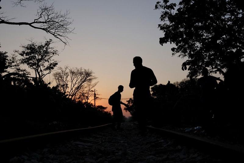 Un grupo de migrantes centroamericanos descansa a lo largo de la vÌa del tren en Macuspana, MÈxico, el 25 de marzo de 2021, en camino a Estados Unidos. (Foto CNS/Carlos Jasso, Reuters)