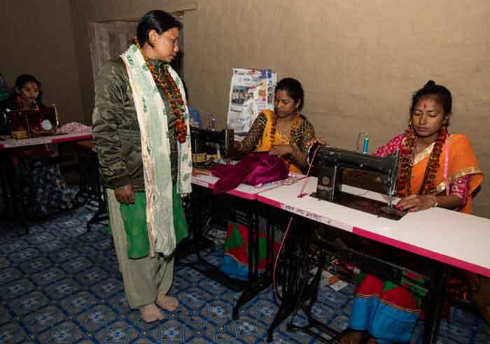 Instructora Gyanu Kumari Chaudhary asiste a estudiantes en el Programa de Entrenamiento en Costura para Mujeres Desfavorecidas en Baniyabhar, distrito Bardiya, Nepal. (Gregg Brekke/Nepal)