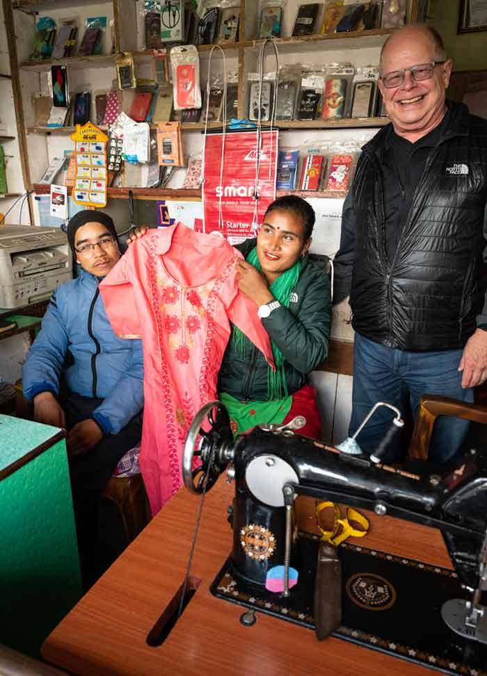 Padre Joseph Thaler (derecha) visita a Dambarkala Thapa, una graduada del Sewing Cutting Training for Differently Abled Persons, y a su esposo Tej Bahadur Ran en su tienda en el distrito Banke, Nepal. La pareja, ambos con discapacidades físicas, recibieron entrenamiento y apoyo de los Padres y Hermanos Maryknoll, ella en sastrería y él en reparación de teléfonos móviles y pequeños aparatos electrónicos. (Gregg Brekke/Nepal)