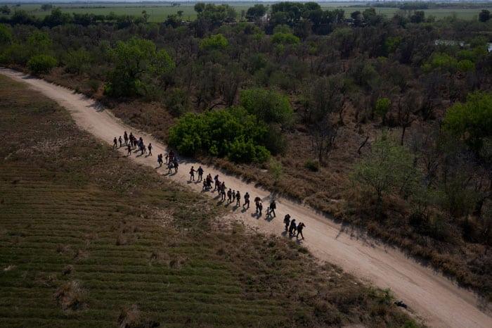 En la frontera: Migrantes de Centroamérica caminan hacia el muro fronterizo entre Estados Unidos y México en Peñitas, Texas, el 26 de marzo de 2021, después de cruzar el Río Grande. (Foto del CNS / Adrees Latif, Reuters)