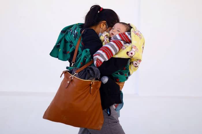 En la frontera: Una migrante de Guatemala que buscaba asilo en los Estados Unidos y fue deportada camina con su bebé en Ciudad Juárez, México, el 27 de marzo de 2021. (Foto de CNS / Edgard Garrido, Reuters)