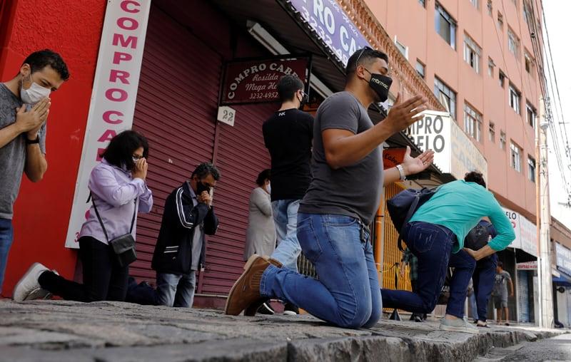 Las personas se arrodillan en oración durante una misa de Pascua fuera del Santuario de Nuestra Señora de Guadalupe en Curitiba, Brasil, el 4 de abril de 2021, durante la pandemia de COVID-19. (Foto del CNS / Rodolfo Buhrer, Reuters)