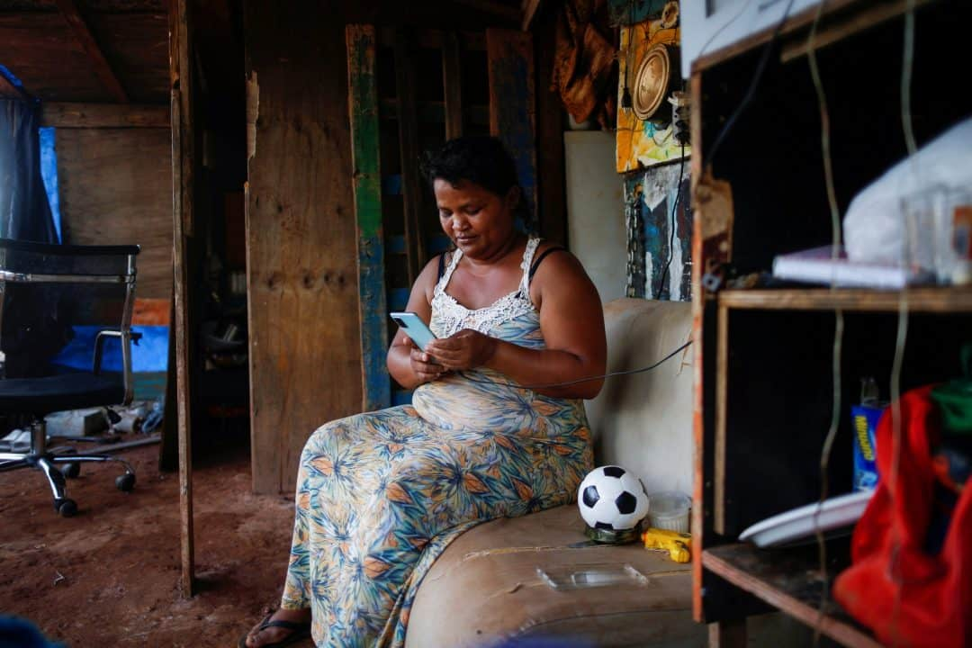 Tatiana Araujo de Sirqueira, 33, uses a cell phone in her home set up on land near Planalto Palace during the coronavirus pandemic in Brasília, Brazil, March 3, 2021. In a message to participants of the World Bank Group and International Monetary Fund 2021 virtual spring meetings, Pope Francis said poor countries cannot be expected to recover from the current financial crisis if the world returns to an economic model in which a small minority of people owns half of the world's wealth. (CNS photo/Adriano Machado, Reuters)