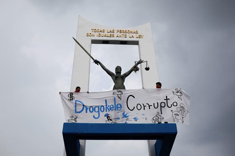 Las personas sostienen una pancarta junto a un monumento en San Salvador, El Salvador, el 2 de mayo de 2021, mientras protestan por la destitución por parte del Congreso salvadoreño de los jueces de la corte constitucional y el fiscal general. (Foto del CNS / José Cabezas, Reuters)