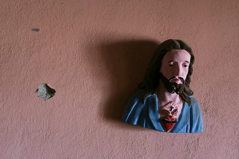 Un busto de Cristo cuelga de una pared junto a un impacto de bala en una casa abandonada cerca de Aguililla, México, 23 de abril de 2021. Los obispos mexicanos han pedido a los ciudadanos que voten y apoyen a los candidatos que promueven el bien común en las elecciones de mitad de período. (Foto del CNS / Alan Ortega, Reuters)