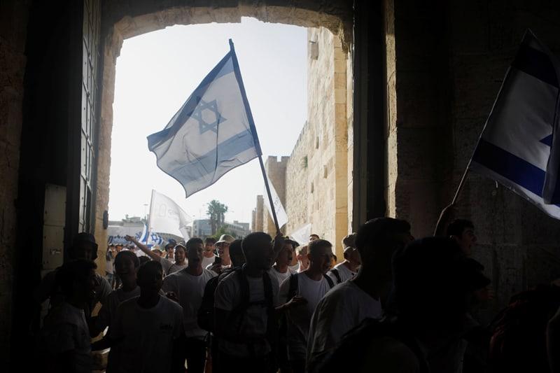 Jóvenes flamean banderas israelíes durante un desfile que marca el Día de Jerusalén, durante un momento en que continúan los ataques israelí-palestinos, cuando entran por la Puerta de Jaffa en la Ciudad Vieja de Jerusalén el 10 de mayo de 2021 (Foto del CNS / Nir Elias, Reuters)