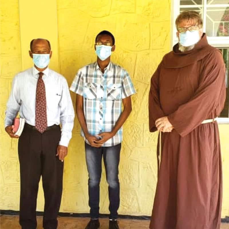 El Padre Colin King saluda al estudiante Alex Gordon y a su papá Mike, dándoles la bienvenida al Monsignor Gladstone Wilson College, donde Mike forma parte de la junta escolar. (Cortesía de Colin King/Jamaica)