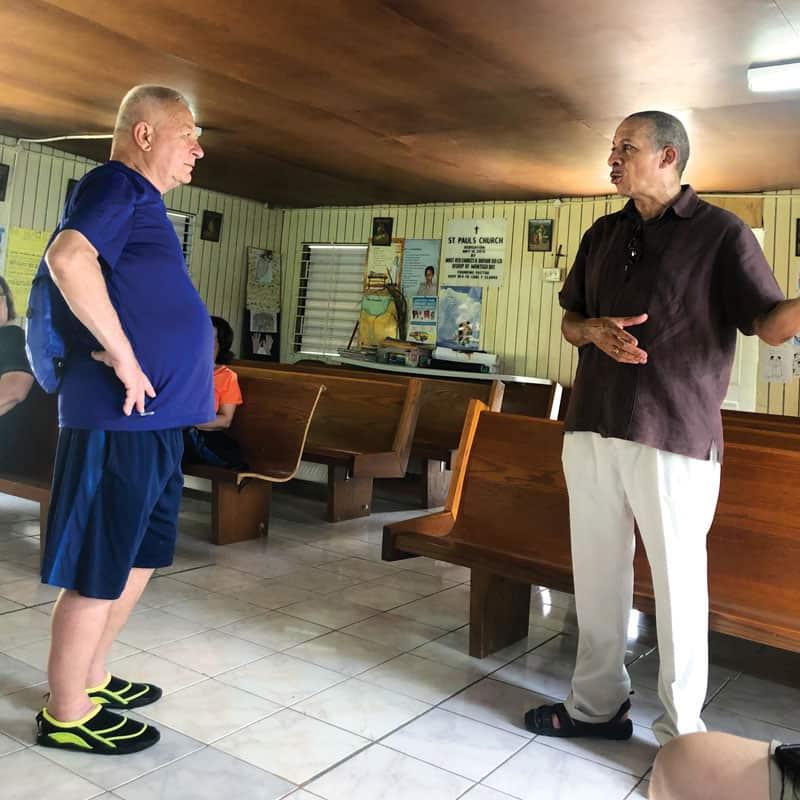 En la Capilla de San Pablo en Glendevon, Diócesis de Montego Bay, el diácono Powell (derecha) explica a un participante del viaje de inmersión sobre la misión de la Iglesia en Jamaica. (Matthew Dulka/Jamaica)